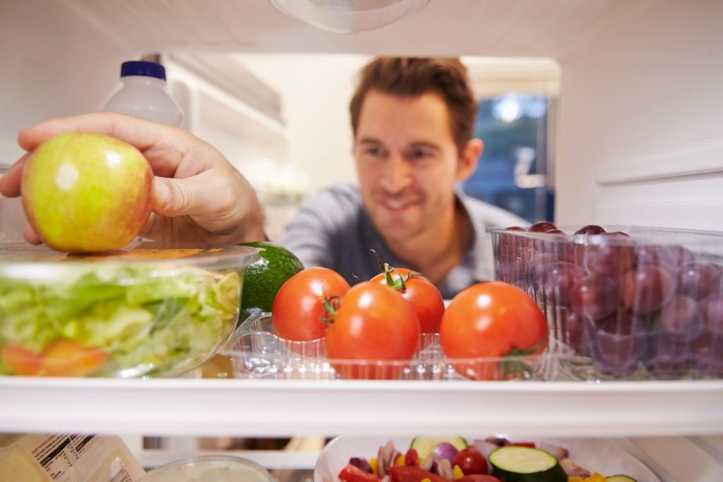 Man getting an apple from the fridge