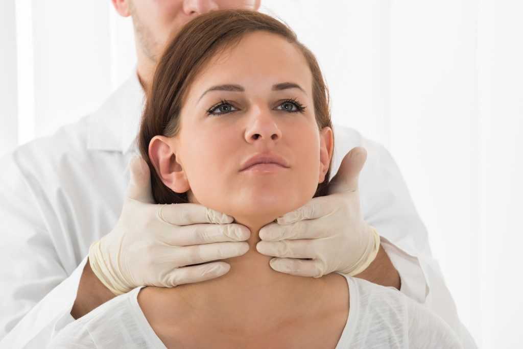 Doctor checking the woman's thyroid