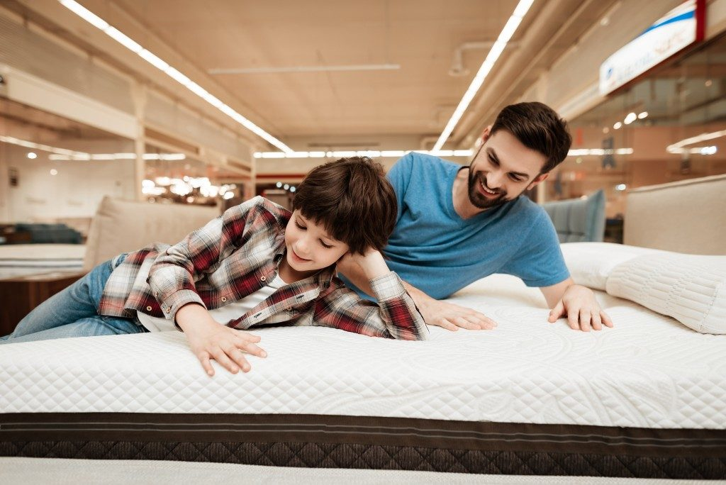 dad and son lying on mattress