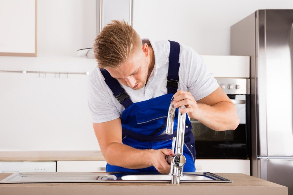 handsome plumber fixing the faucet