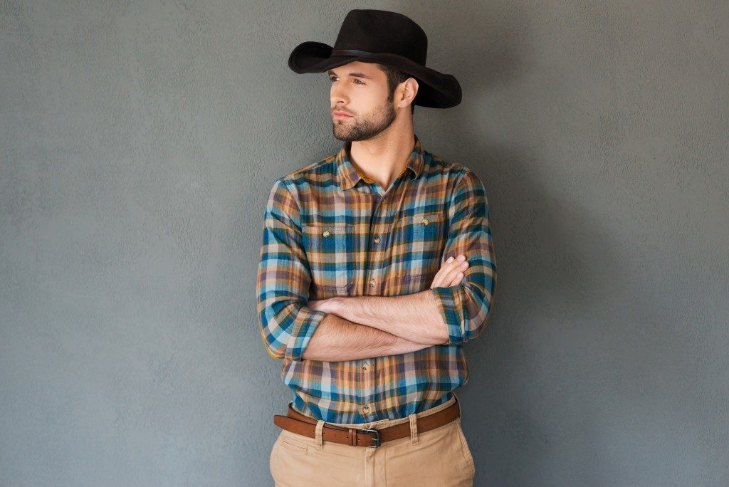 young man in cowboy hat keeping arms crossed and looking away