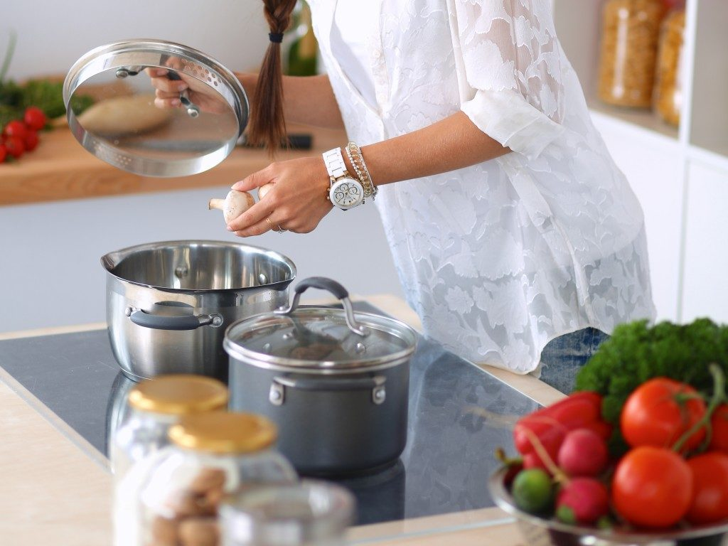 Woman about to cover the cooking pot