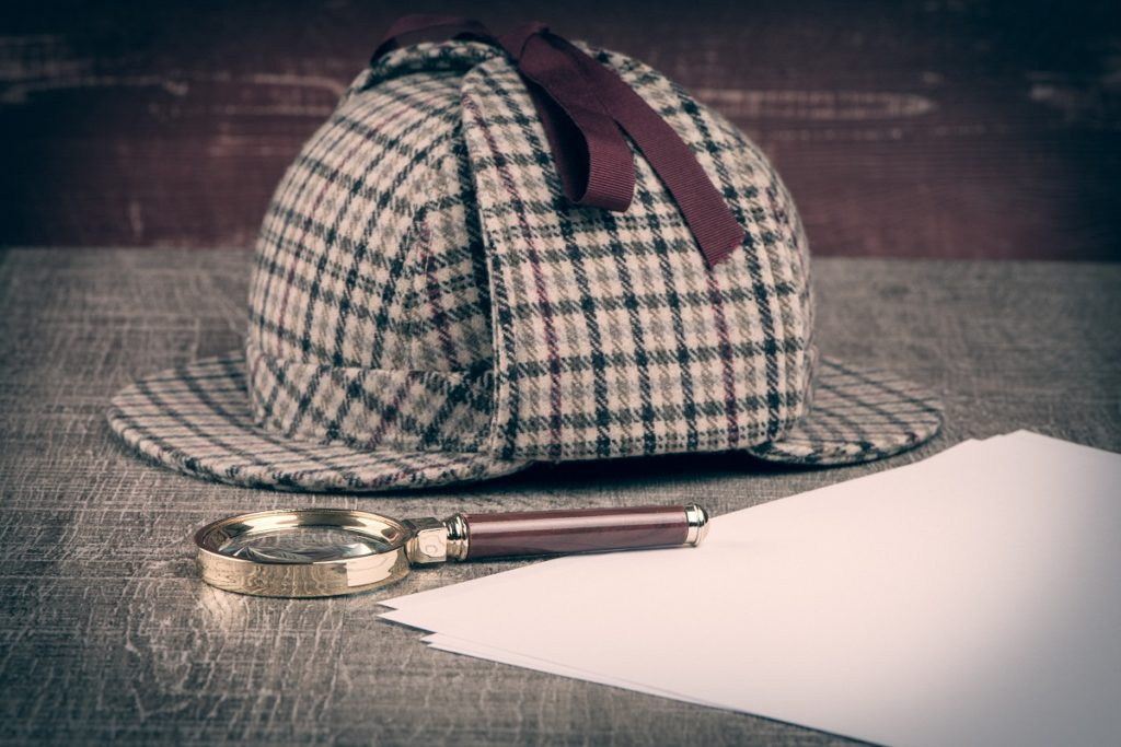 Private investigator cap and magnifying glass