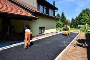 Team of Workers making and constructing asphalt road construction with steamroller