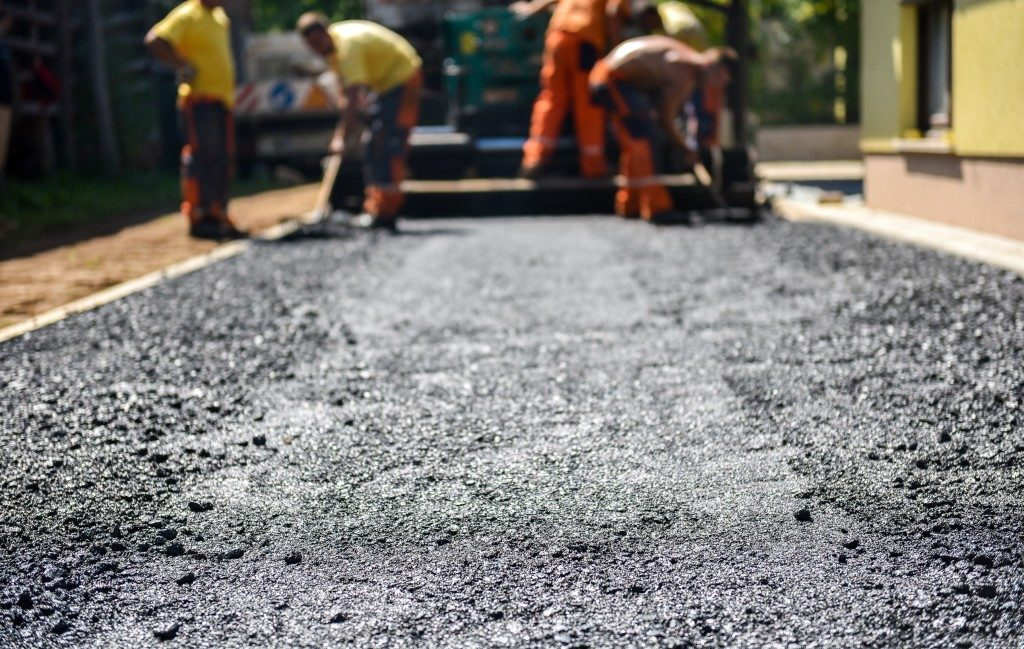 Team of Workers making and constructing asphalt road construction with finisher
