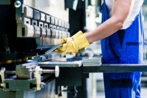 man working in a sheet metal press brakes machine