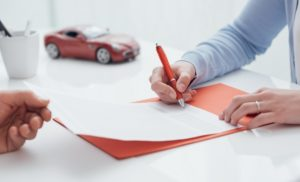 man signing a contract for his car purchase