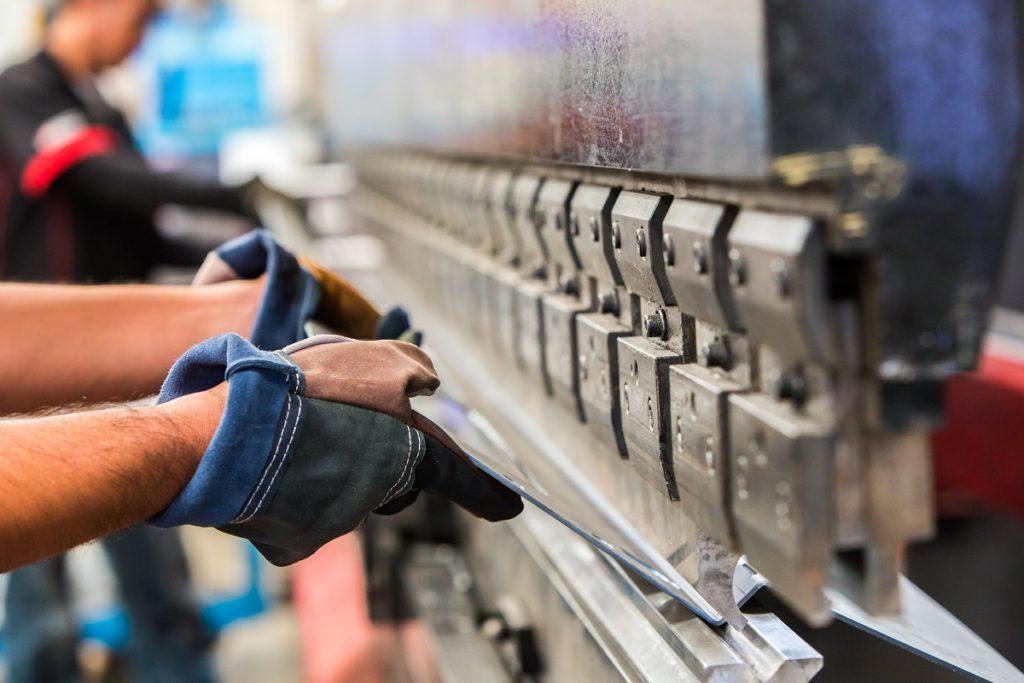 men working in a sheet metal press brakes machine