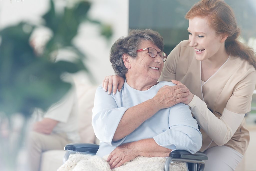 Elderly woman happily holding the hand of younger woman