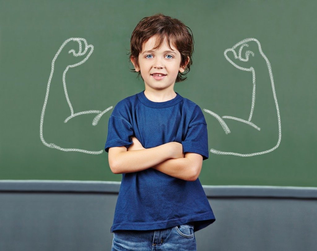 boy with muscles drawn on chalkboard