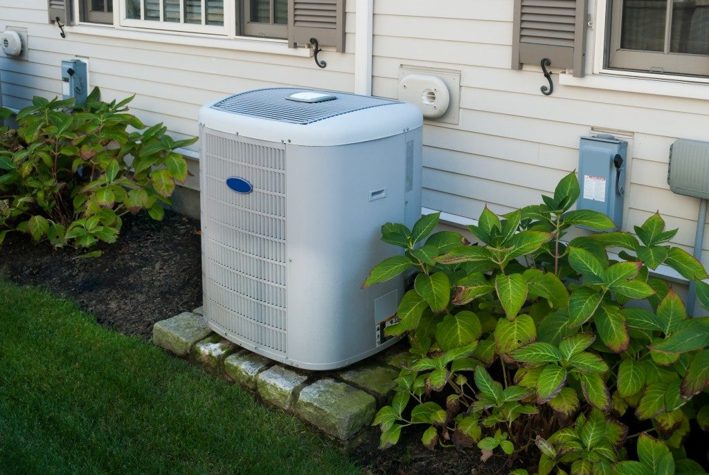 white heat pump at the back of a home