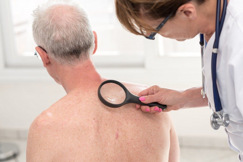 Doctor checking patient's skin