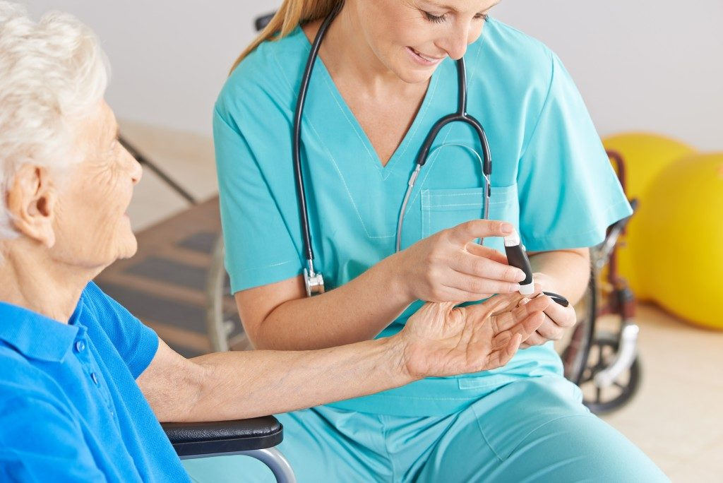 nurse taking blood sugar from old woman