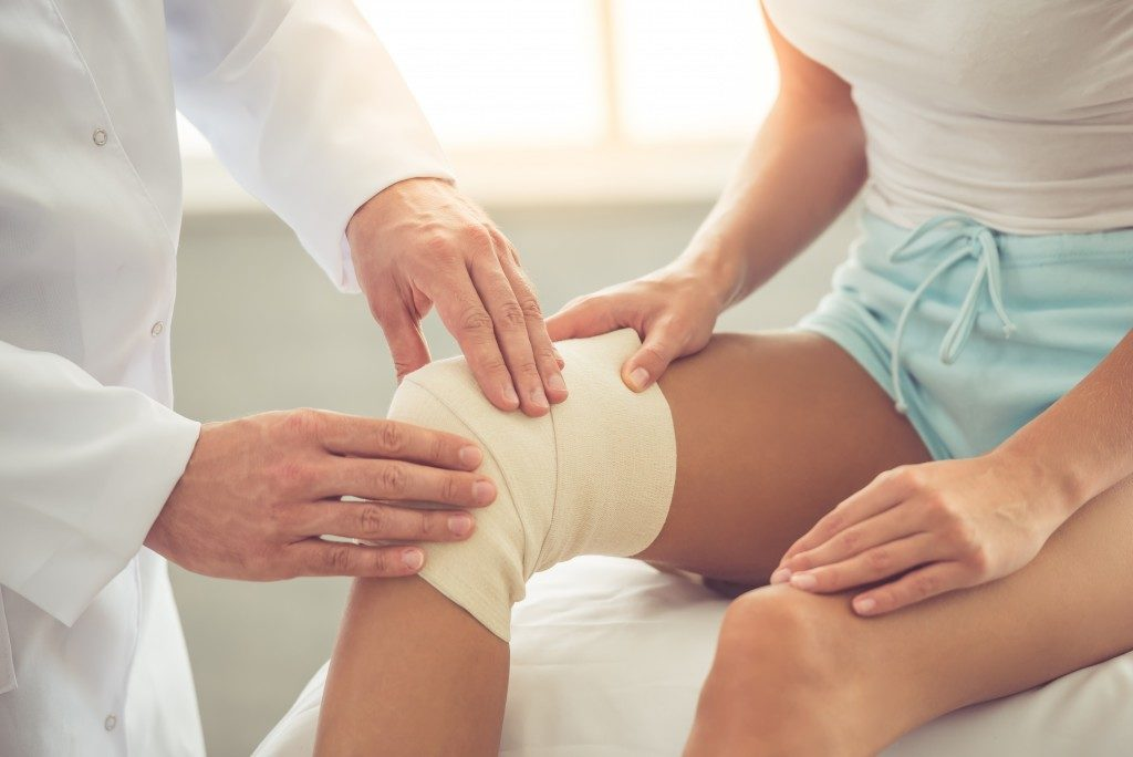 Woman with injured knee at the doctor