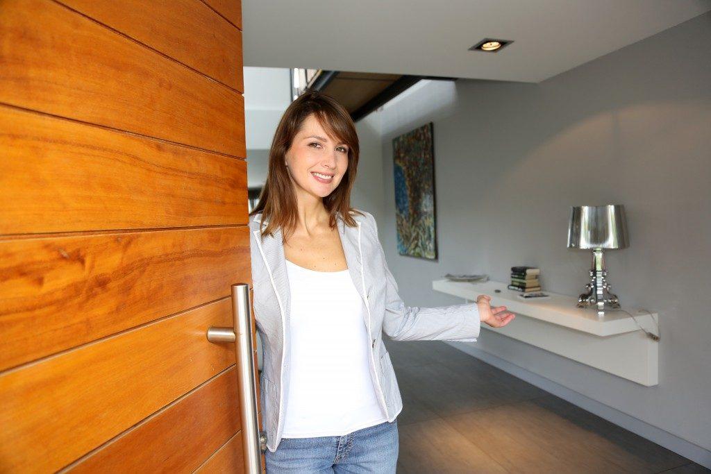 Woman opening wooden door