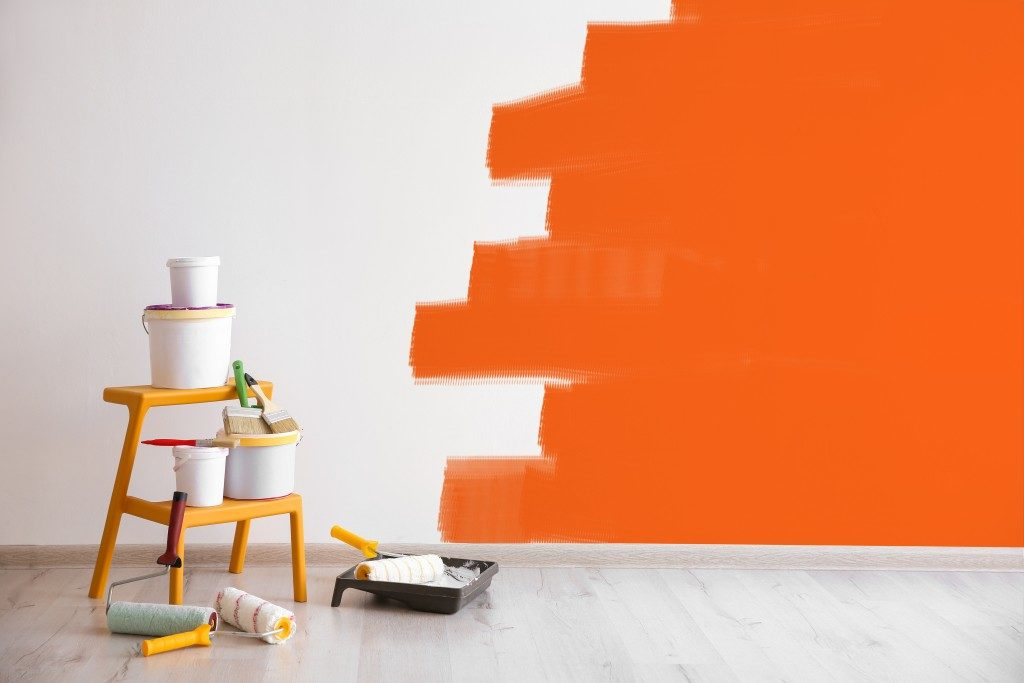 buckets of paint, paint rollers and an unfinished wall