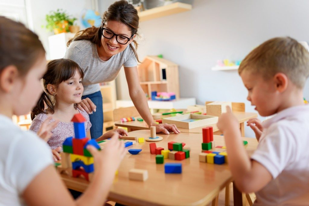 children and teacher in preschool classroom playing blocks