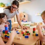 children and teacher in preschool classroom playing blocks