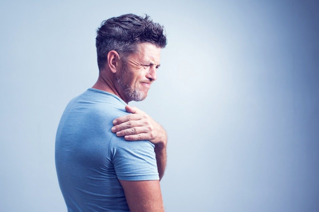 man experiencing pain in his shoulder