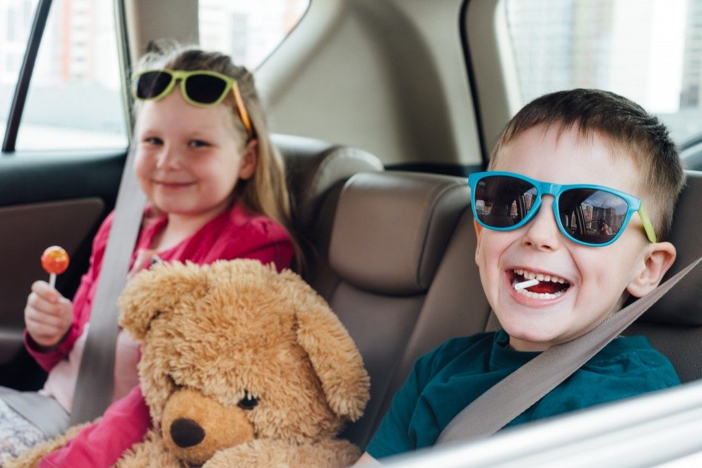 kids seating at the backseat of a car