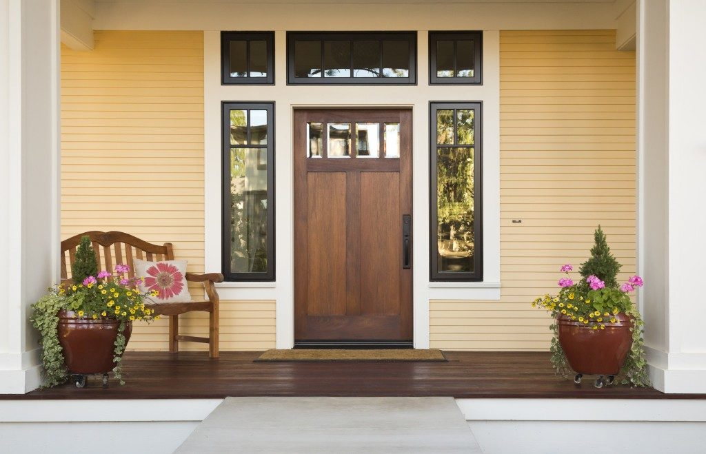 Front view of a wooden front door on a yellow house with reflections in the window and a wide view of the porch and front walkway