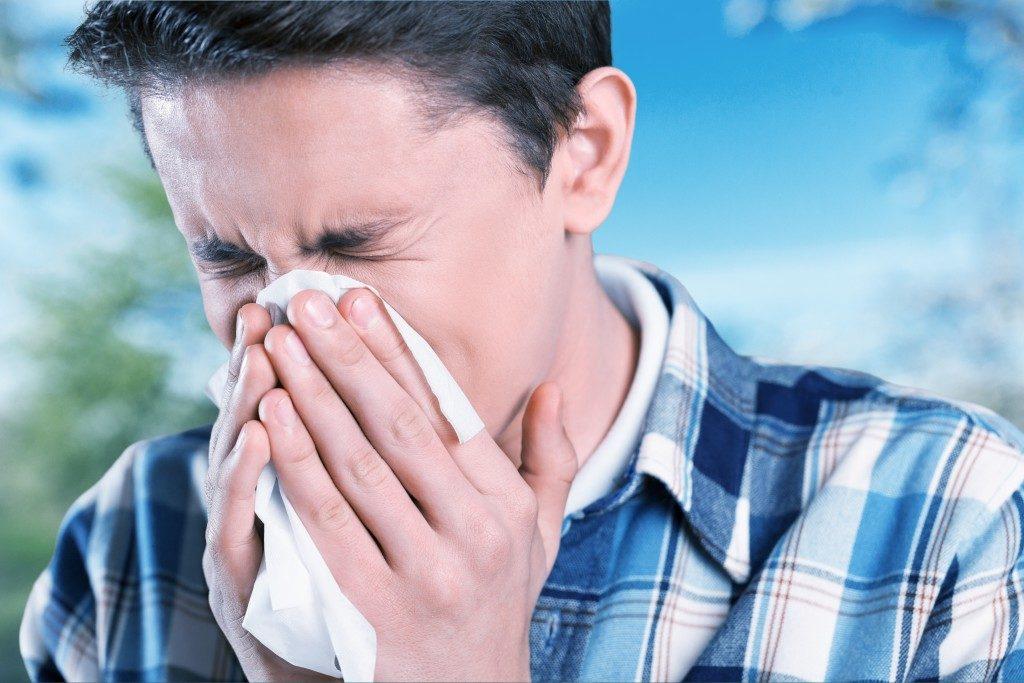 man sneezing into the tissue