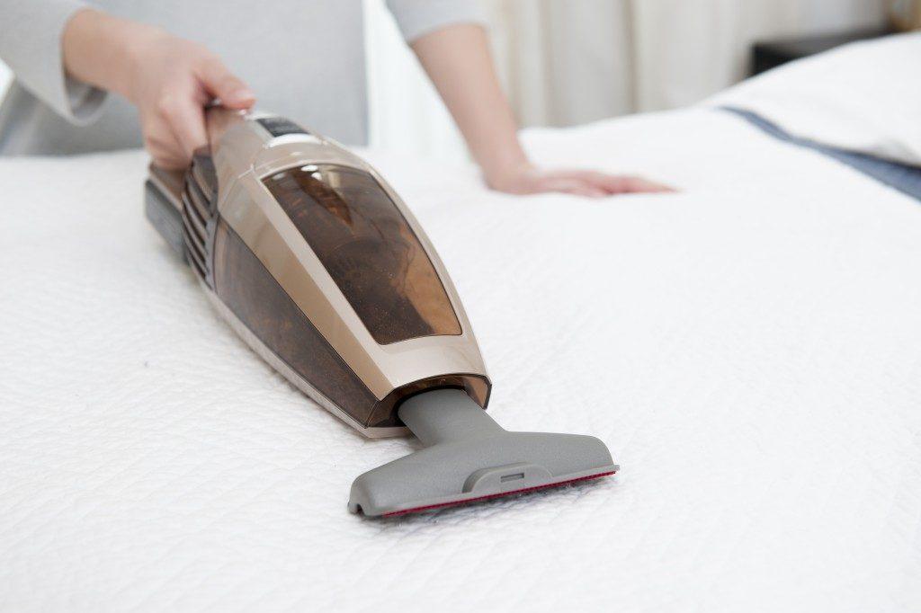 woman vacuuming the mattress