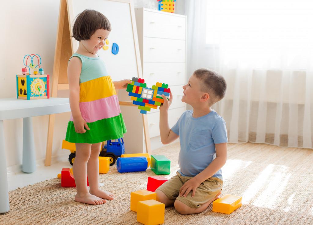 children holding a heart lego