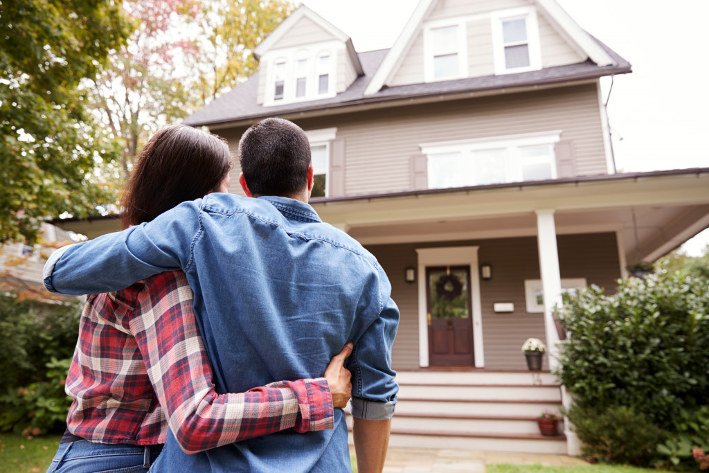 couple standing facing in front of a home