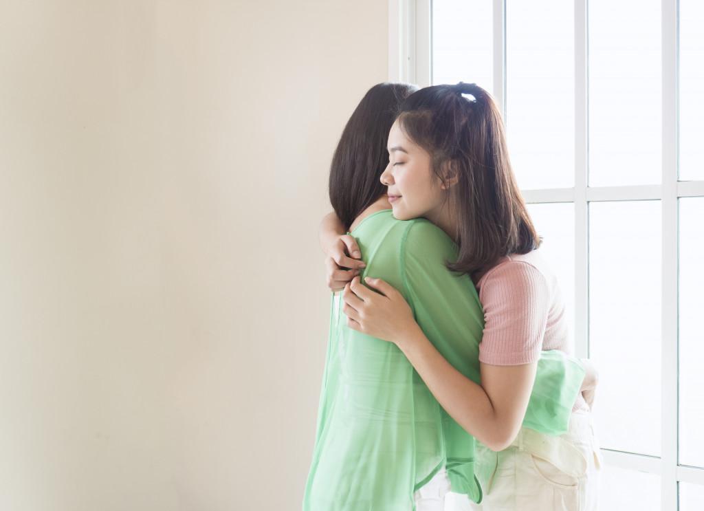mom and teen hugging