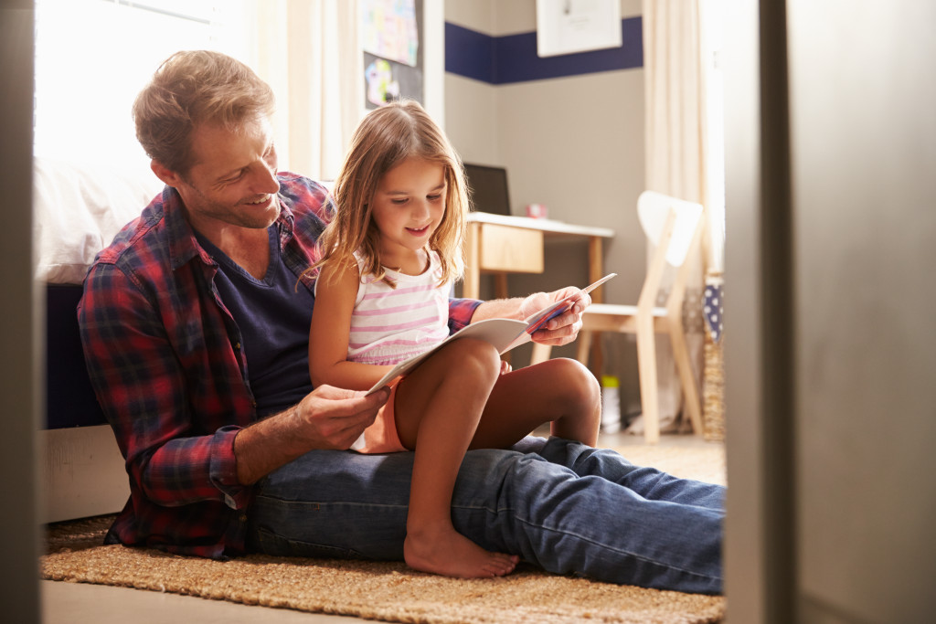 daughter and father reading book