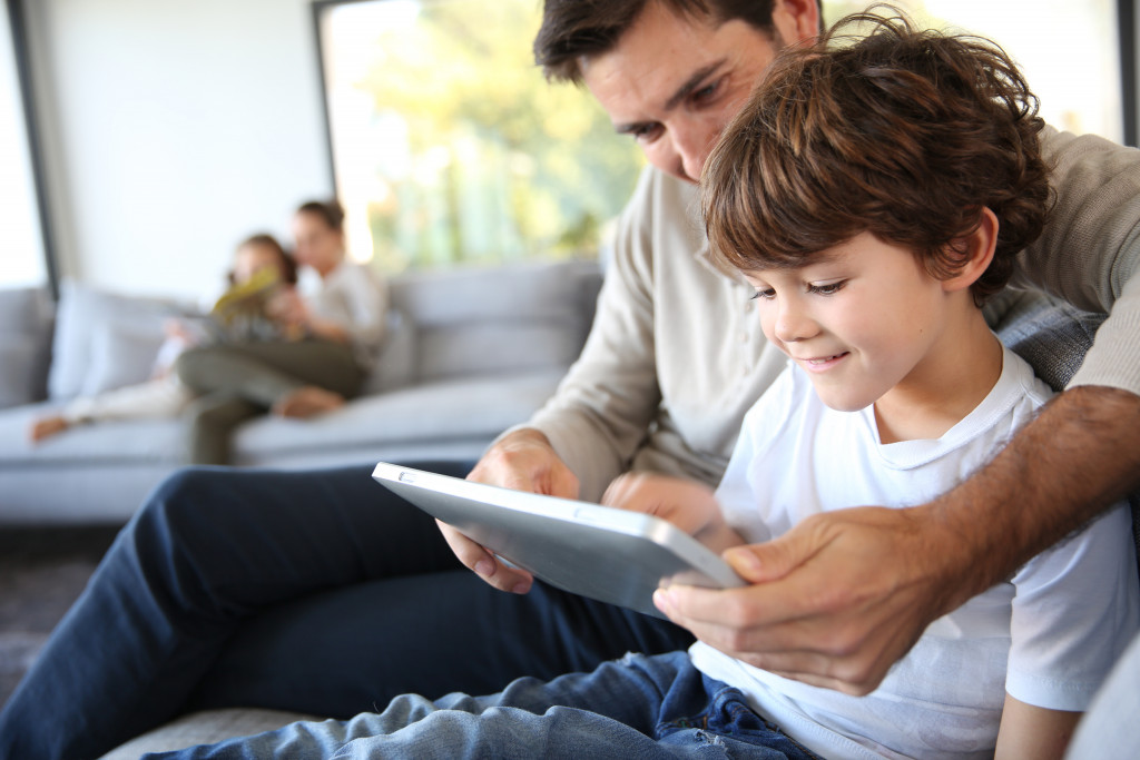 father teaching son with tablet